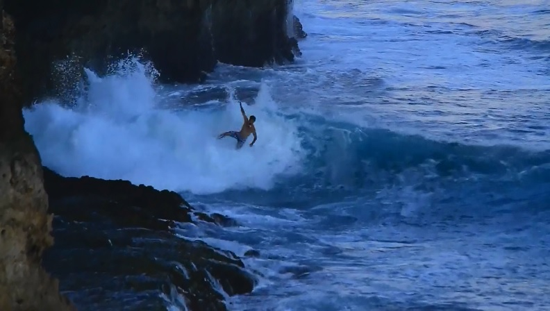 Mason Ho surfing in front of cliff